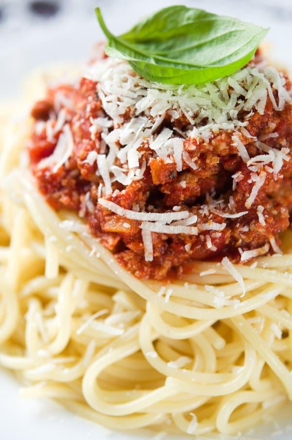 Espaguetis boloñés con parmesano y albahaca imagen de archivo