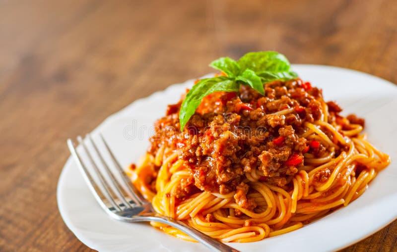 Espaguetis boloñés de las pastas en la placa blanca en fondo de madera de la tabla foto de archivo libre de regalías