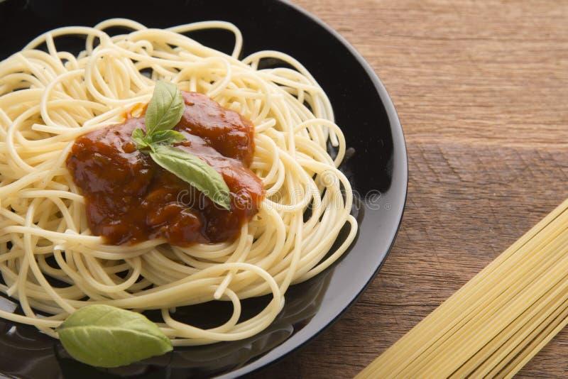 Espaguetis boloñés en placa negra en fondo de madera de la tabla, espaguetis con la salsa mezclada picante y carne fotografía de archivo