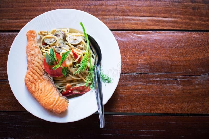 Espaguetis con curry verde y un salmón grande en un plato blanco colocado en una tabla de madera vieja Alimento tailand?s - frita imagen de archivo