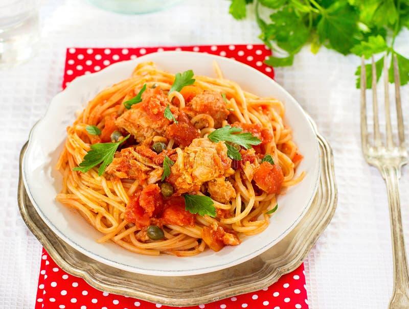 Espaguetis con el atún, alcaparras de las pastas en salsa de tomate fotos de archivo