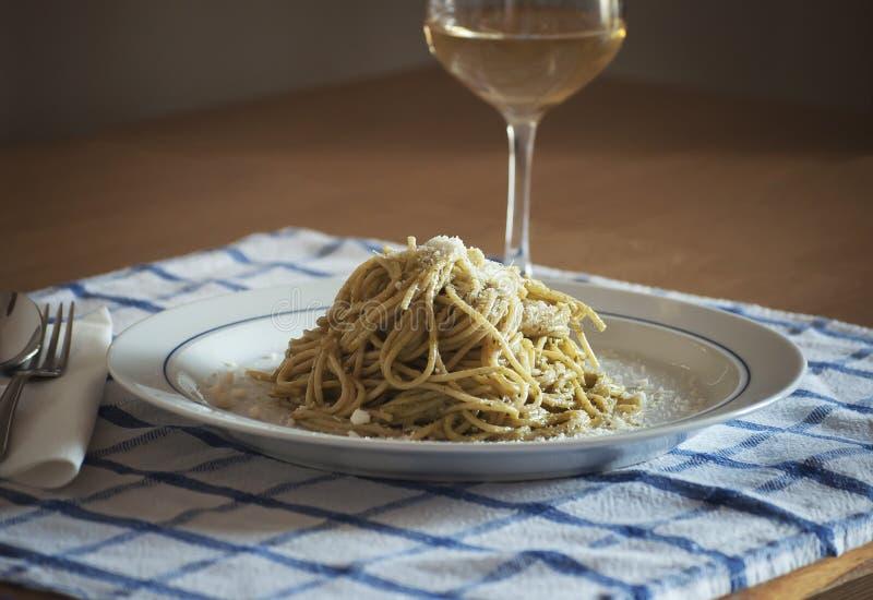 Espaguetis con el Pesto Genovese y el vidrio del queso de romano de Pecorino de vino blanco de Vernaccia Toscana imágenes de archivo libres de regalías