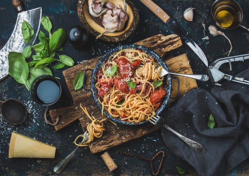 Espaguetis con el tomate y la albahaca e ingredientes para hacer las pastas imagen de archivo libre de regalías