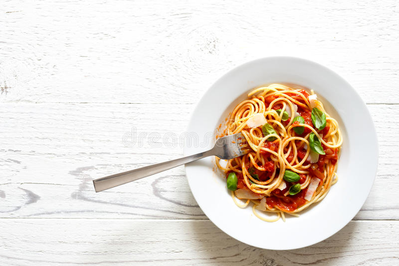 Espaguetis con la bifurcación, la salsa de tomate, la albahaca fresca y el queso isola imagen de archivo libre de regalías