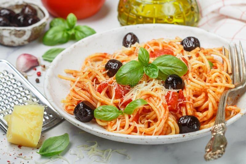Espaguetis con la salsa de tomate con ajo, albahaca, especias, las aceitunas, el aceite de oliva y el queso parmesano en una plac fotos de archivo