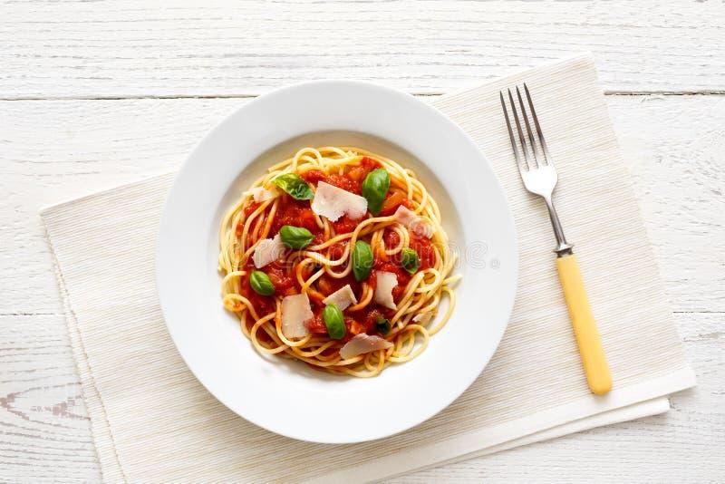 Espaguetis con la salsa de tomate, la albahaca fresca y el queso Con la bifurcación s imagen de archivo libre de regalías