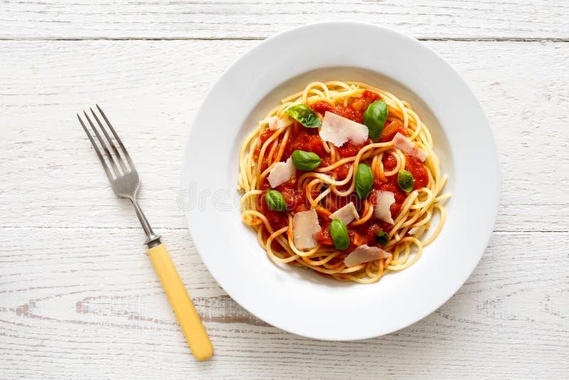Espaguetis con la salsa de tomate, la albahaca fresca y el queso Con la bifurcación s imagenes de archivo