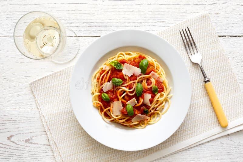 Espaguetis con la salsa de tomate, la albahaca fresca y el queso Vidrio de wh foto de archivo