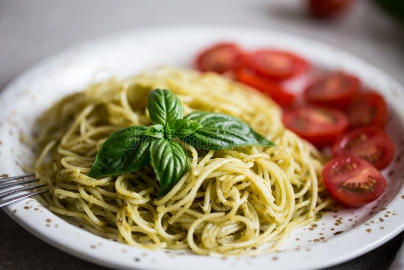 Espaguetis con la salsa del pesto, las hojas de la albahaca y los tomates hechos en casa fotos de archivo