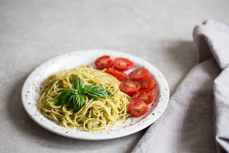 Espaguetis con la salsa del pesto, las hojas de la albahaca y los tomates hechos en casa imagenes de archivo