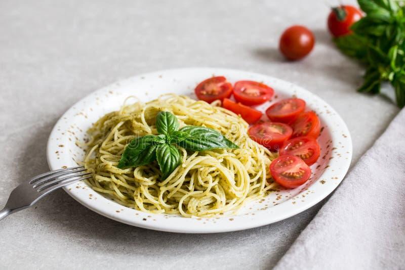 Espaguetis con la salsa del pesto, las hojas de la albahaca y los tomates hechos en casa foto de archivo libre de regalías