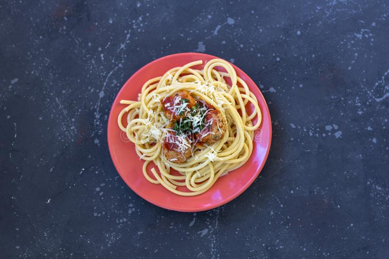 Espaguetis con las albóndigas, la salsa de tomate y el queso parmesano en una placa roja foto de archivo