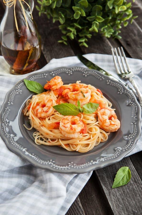 Espaguetis con las gambas y los tomates foto de archivo