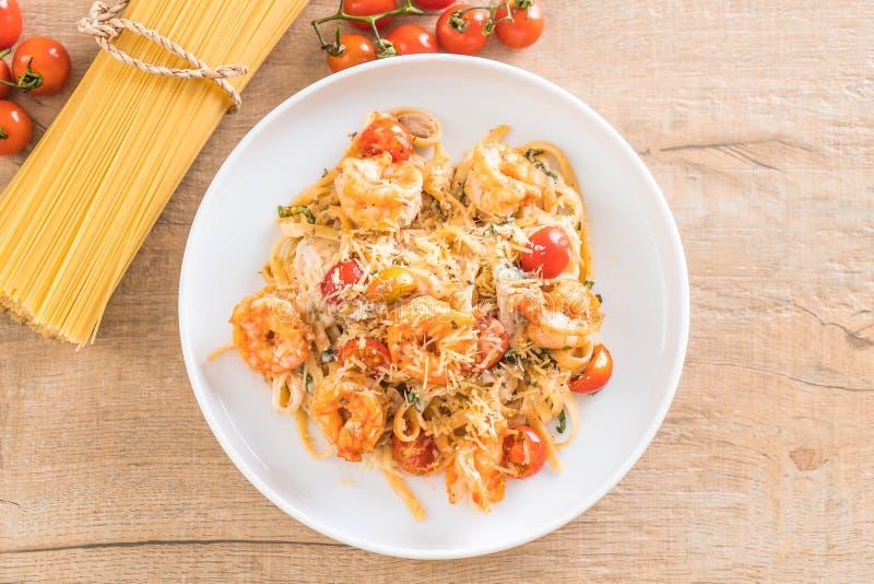 espaguetis con los camarones, los tomates, la albahaca y el queso fotos de archivo libres de regalías