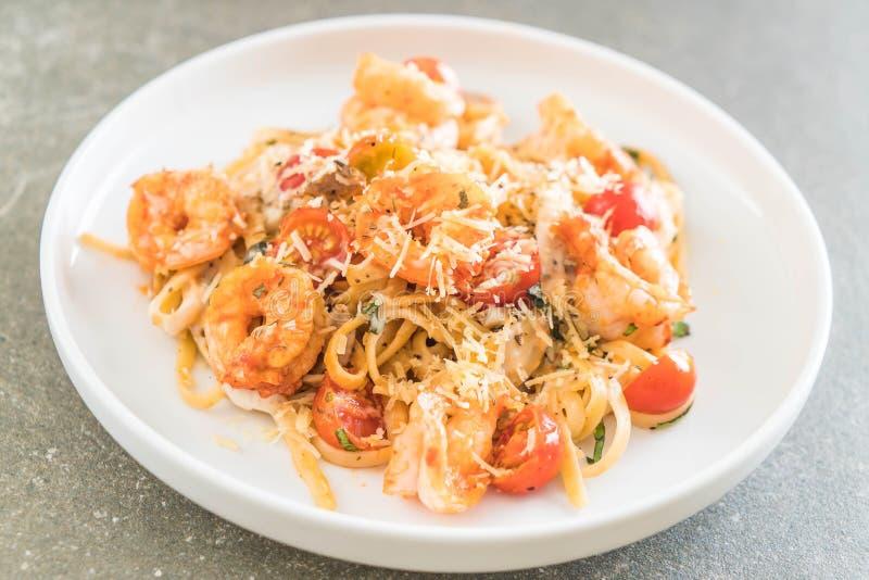 espaguetis con los camarones, los tomates, la albahaca y el queso imagenes de archivo