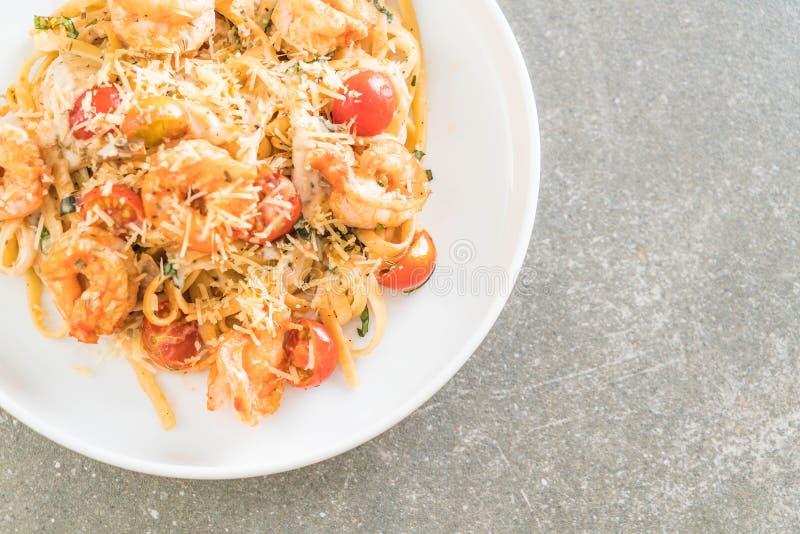 espaguetis con los camarones, los tomates, la albahaca y el queso foto de archivo libre de regalías