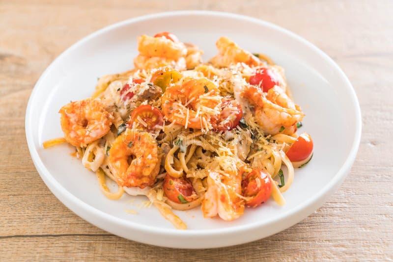 espaguetis con los camarones, los tomates, la albahaca y el queso fotografía de archivo