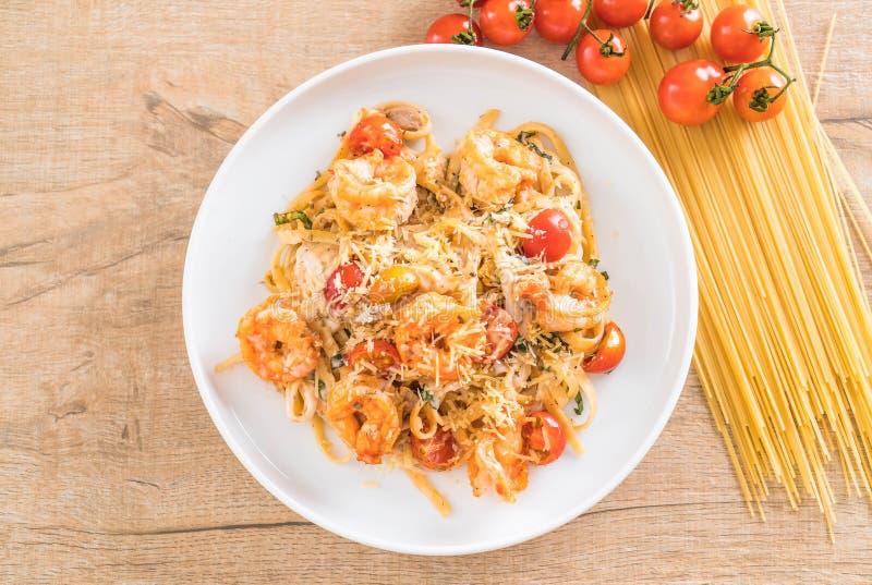 espaguetis con los camarones, los tomates, la albahaca y el queso imagen de archivo