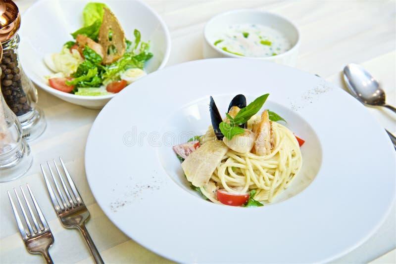 Espaguetis con los mariscos y los tomates imagen de archivo
