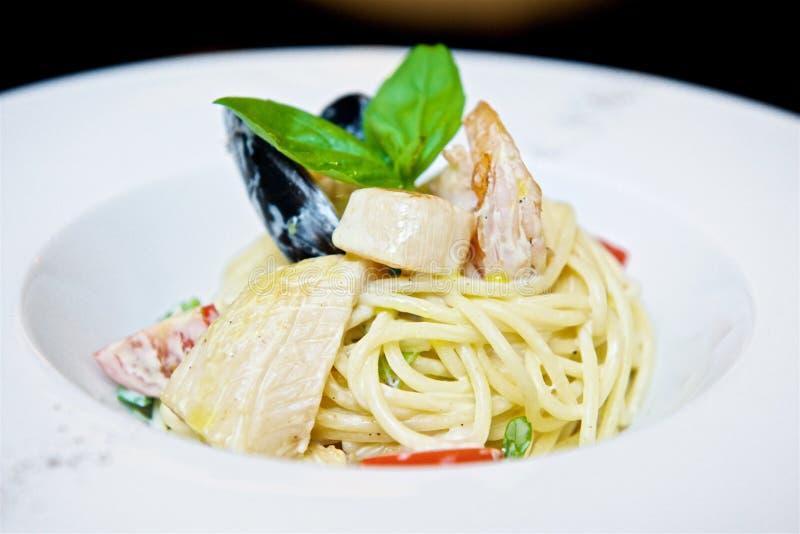 Espaguetis con los mariscos y los tomates imagenes de archivo