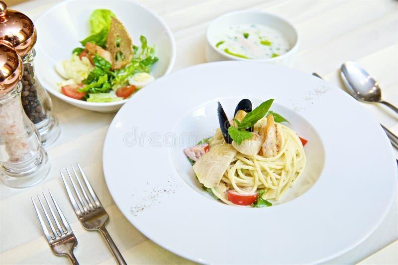 Espaguetis con los mariscos y los tomates foto de archivo