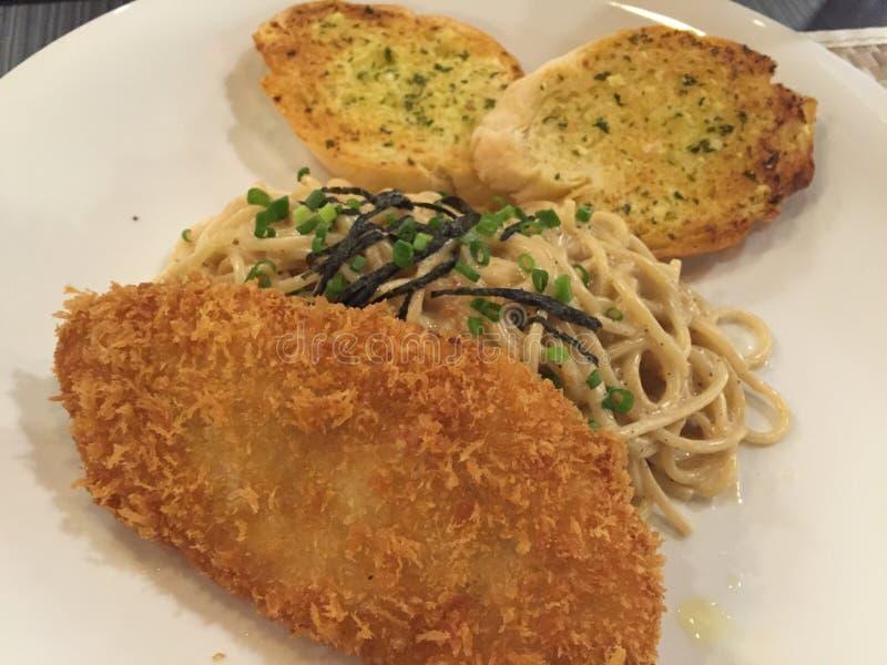 Espaguetis con los pescados fritos imagen de archivo