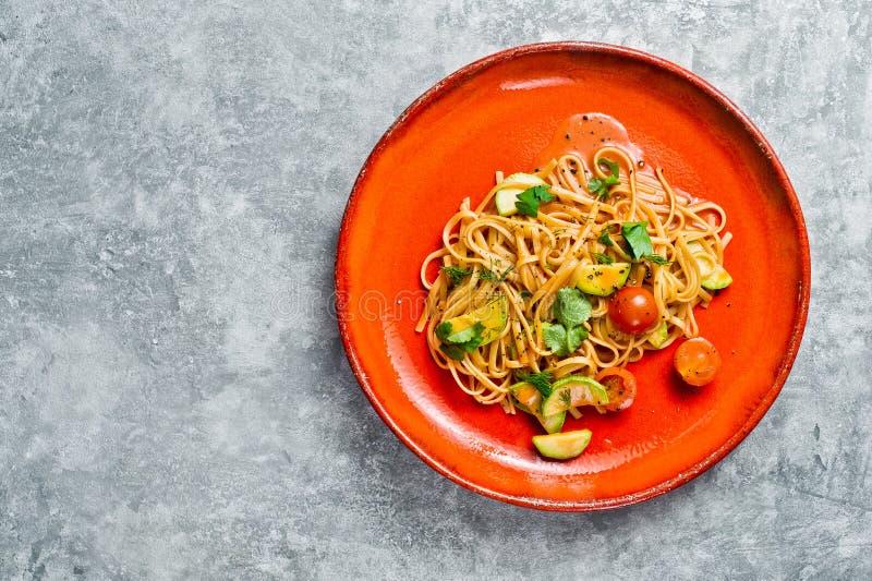Espaguetis con los tomates, el avacado y el calabac?n, cocina vegetariana Fondo gris, visi?n superior, espacio para el texto fotografía de archivo libre de regalías