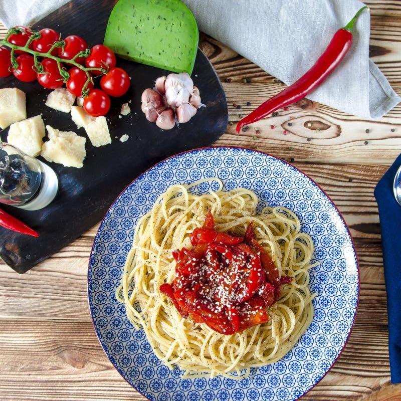 Espaguetis con mentira roja de la salsa de la pimienta dulce y del sésamo en una placa azul en una tabla de madera fotografía de archivo