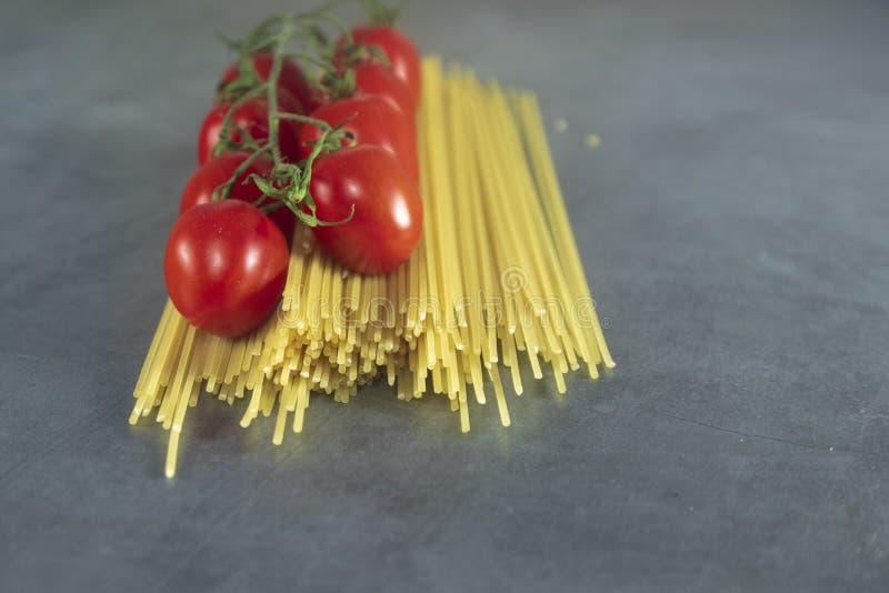 Espaguetis crudos con los tomates de cereza fotografía de archivo libre de regalías