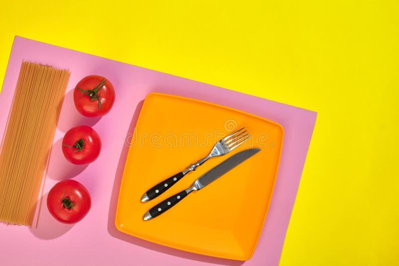 Espaguetis crudos y tomates rojos en fondo rosado y amarillo Espagueti fino Concepto del fondo de la comida Ingredientes imagen de archivo libre de regalías