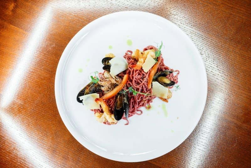 Espaguetis de Brown con el calamari con los mejillones con los camarones y verdes en una placa en un restaurante Alimento gastrón imagenes de archivo
