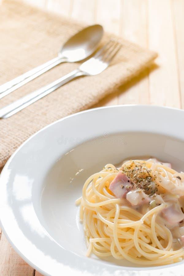 Espaguetis de Cabonara servidos en la tabla fotografía de archivo