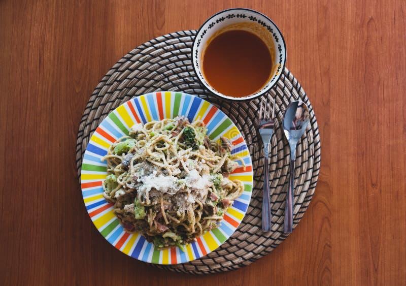 Espaguetis de Carbonara en la placa colorida y gazpacho en el cuenco todo en la tabla de madera foto de archivo