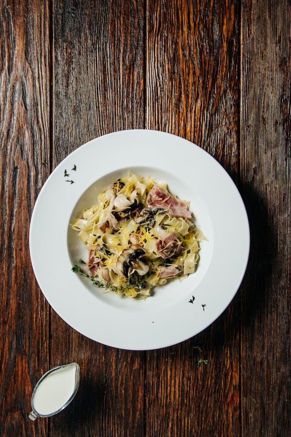 Espaguetis de las pastas con la salsa de seta cremosa en la placa de cerámica blanca sobre la tabla vieja de la oscuridad del gru fotos de archivo libres de regalías