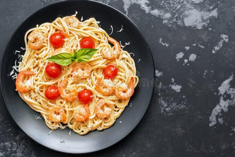 Espaguetis de las pastas con los camarones y los tomates en un fondo concreto negro Visión superior, espacio de la copia foto de archivo