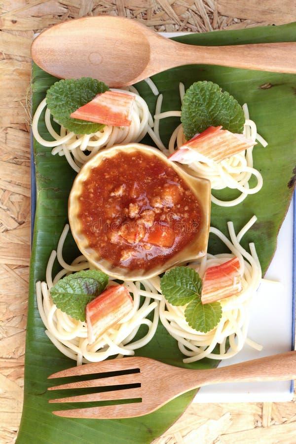Espaguetis de las pastas con los palillos y la salsa del cangrejo imagen de archivo