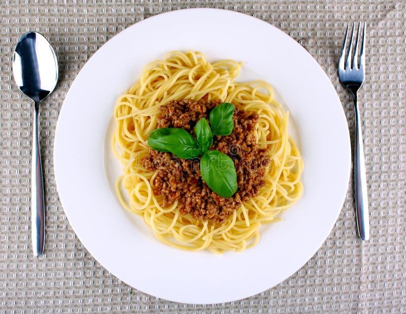 Espaguetis deliciosos boloñés con albahaca en la placa blanca imagenes de archivo