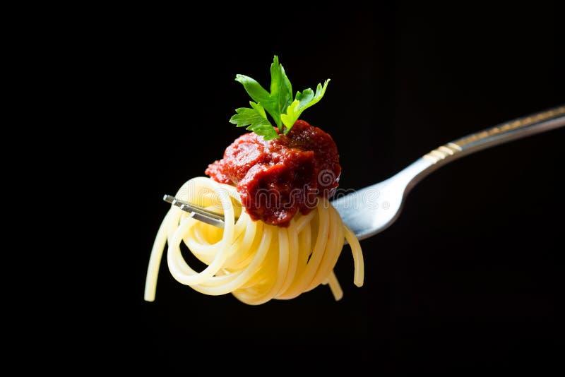 Espaguetis deliciosos en el primer de la bifurcación negro imagenes de archivo