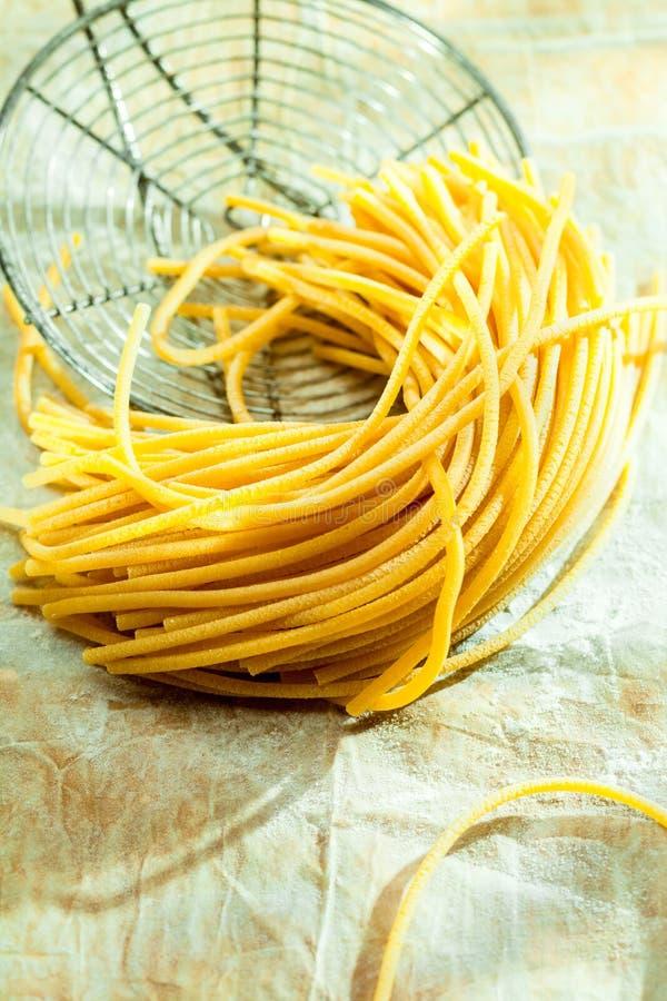 Espaguetis italianos cocinados en un tamiz viejo del alambre fotos de archivo