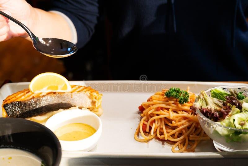 Espaguetis italianos con un filete de color salmón asado a la parrilla sabroso y una patata dulce triturada imagenes de archivo