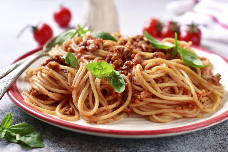 Espaguetis italianos tradicionales boloñés con la salsa, la albahaca y el queso parmesano de la carne imagenes de archivo