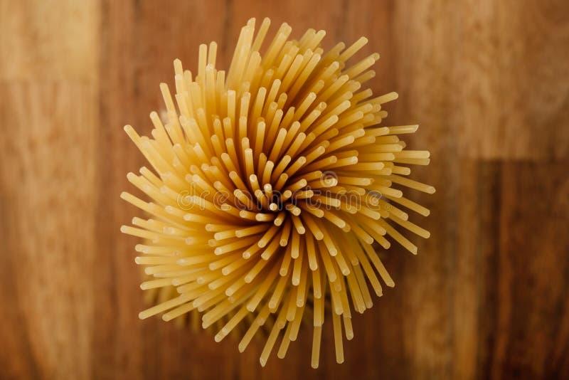 Espaguetis largos amarillos en un fondo de madera, visión superior Pastas italianas amarillas Espagueti largo Espaguetis crudos b foto de archivo