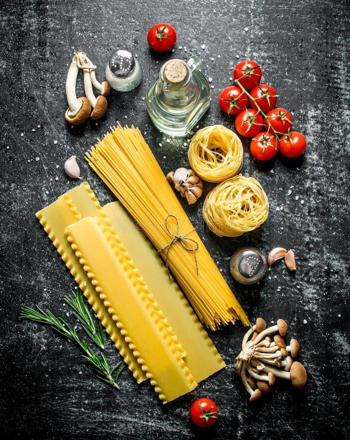 Espaguetis, lasa?as, tallarines crudos con aceite, tomates y setas foto de archivo libre de regalías