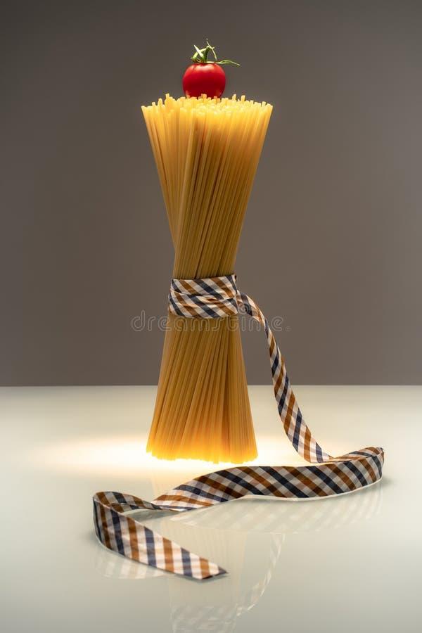 Espaguetis llenos de la moda atados con la cinta en fondo bicolor con el tomate en el top foto de archivo libre de regalías