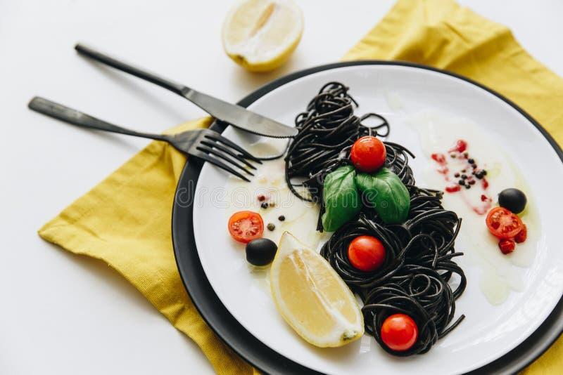 Espaguetis negros con aceite de oliva, tomates fotografía de archivo libre de regalías