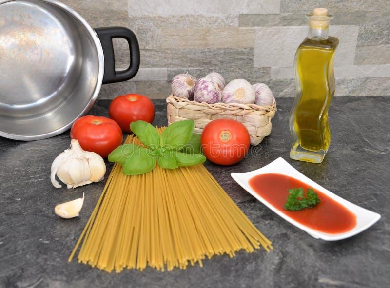 Espaguetis que cocinan en la vista delantera de la tabla de cocina imagen de archivo libre de regalías