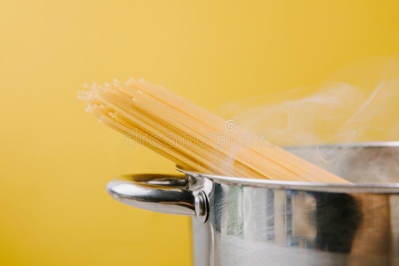 espaguetis que hierven en stewpot en amarillo imagenes de archivo