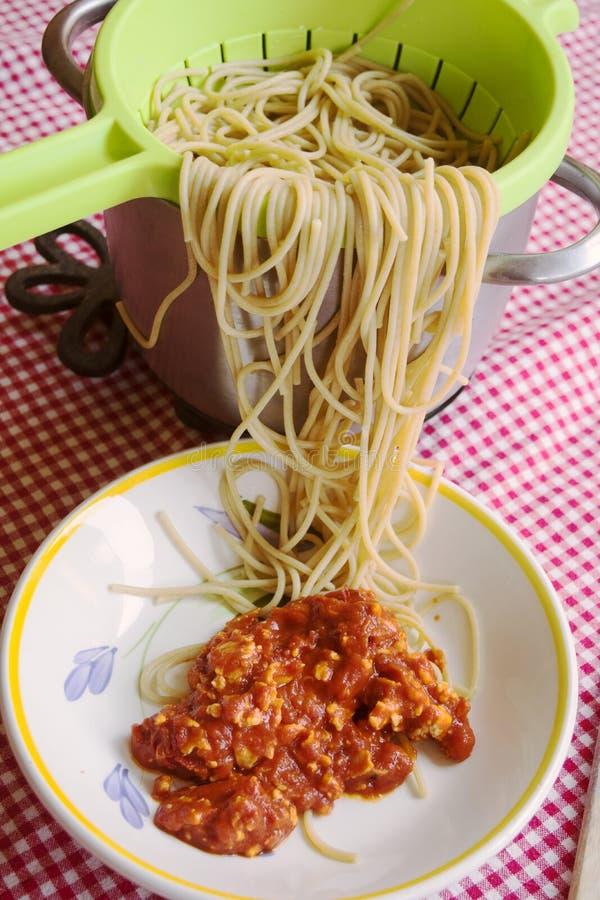 Espaguetis que se pegan fuera de un colador y de un plato de la salsa de tomate fotografía de archivo