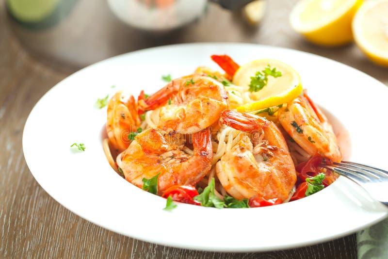 espaguetis sofritos con los camarones y los tomates asados a la parrilla - estilo italiano de la comida de la fusión foto de archivo