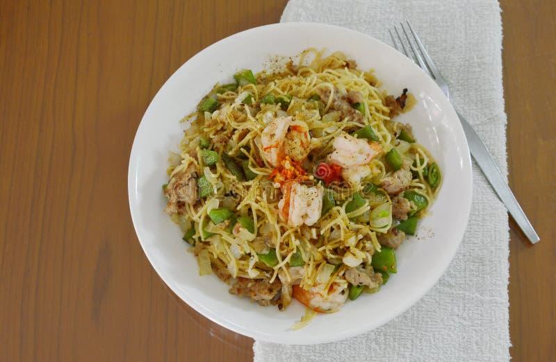 Espaguetis sofritos picantes de la pimienta con el camarón y el cerdo picadito en la placa imagenes de archivo